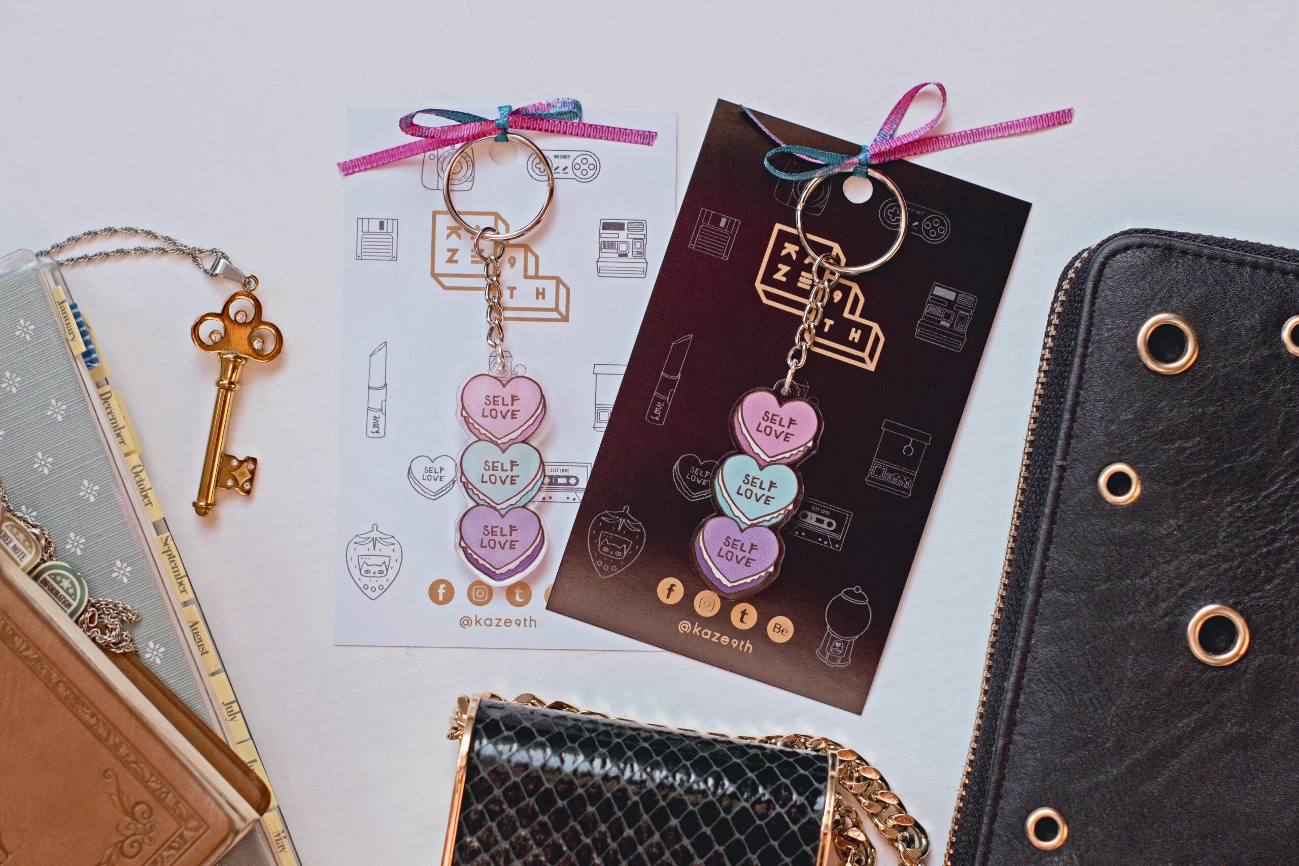 flat lay productos perfume y billetera enmarcan a dos llaveros macaroon self love plano zenital
