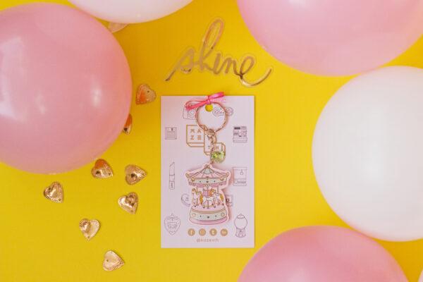 fondo amarillo con globos blancos y rosado llavero acrilico carrusel