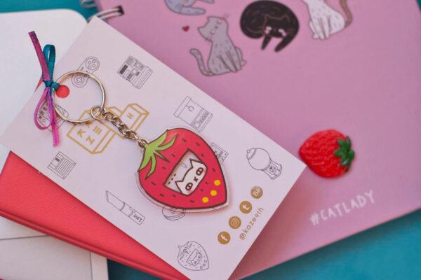 fondo turquesa flat lay libreta rosa y acrilico llavero frutilla tamagochi fresa