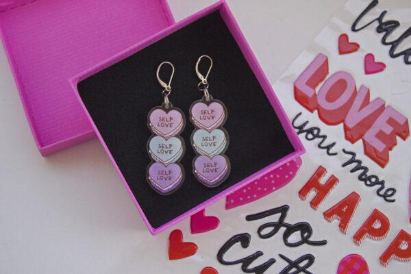 caja rosada con tela negra y aretes acrilicos self love macarones de corazones