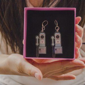 plano detalle mostrando una caja de carton rosada con aretes acrilico telefono analogo color turquesa