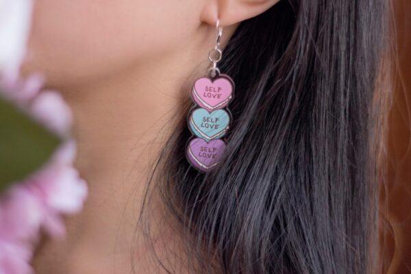 detalle de la oreja con arete self love acrilico de tres corazones de macarones