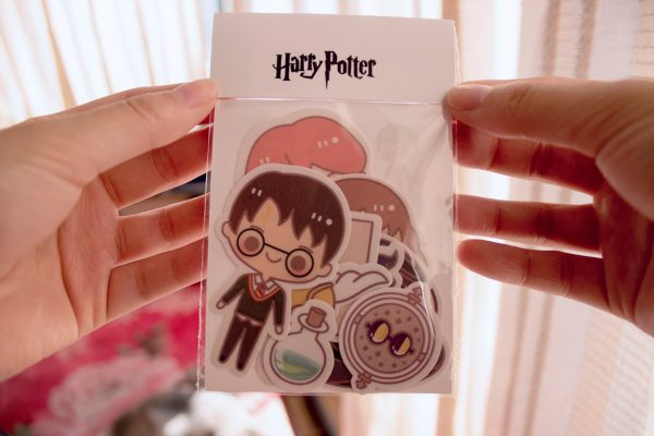 manos sosteniendo una funda de stickers de harry potter